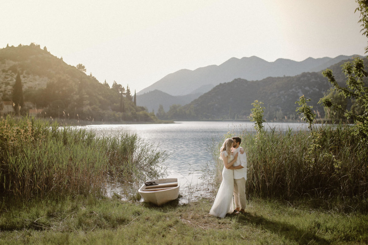 Bride and groom hugging tenderly while standing on the shore of beautiful Bacina Lakes. In the background there are lakes and nature as well as small boat with oars. This photo was taken on their elopement wedding in Croatia.