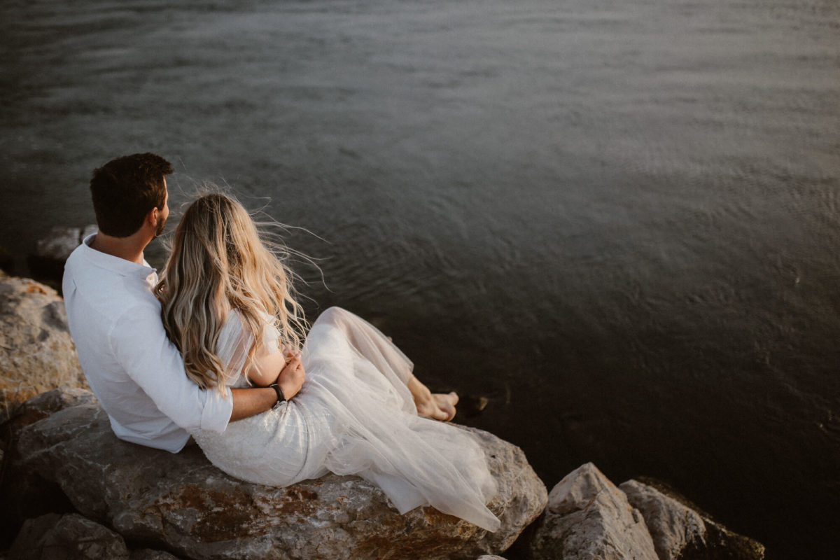 A bride and groom sitting on the rocks near the sea and huggin while wind is blowing their hair away. The romantic sunset photo is taken during their elopement wedding in Croatia