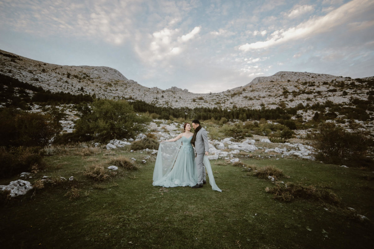 bride in green tulle dress hugs the groom in grey suit in the middle of natural green surrounding while on their elopement in Nature Park Biokovo in Croatia.