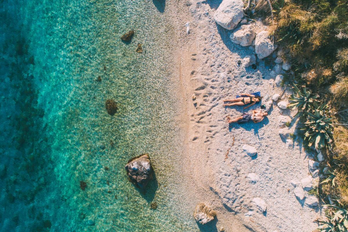 makarska riviera beaches, a couple laying on the beach in croatia